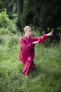 Woman practicing Tai Chi on grassy field Kuvituskuvat