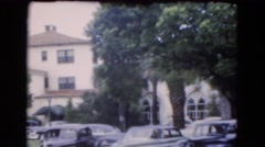 1951: a parking lot full of cars set against a large building or resort hotel Stock Footage