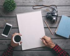 Cropped image of man holding coffee cup while writing on paper at table Stock Photos