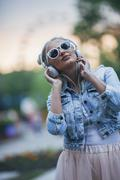 Fashionable young woman wearing sunglasses while listening to music through Stock Photos