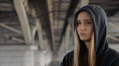 A teenage girl in a hoody with the hood on and loose multicolored hair rubbing Stock Footage
