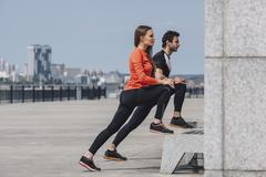 Side view of determined friends stretching legs while exercising on promenade Stock Photos