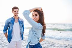 Couple standing and flirting on the beach Stock Photos