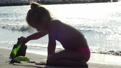 Child playing sand on the beach. Little girl builds sand castle by himself Stock Footage