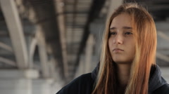 A teenager girl in a hoody with the loose multicolored hair looking into the Stock Footage