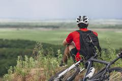 Rear view of man sitting by mountain bike on hill Stock Photos