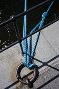Blue rope tied to metal ring by railing against water Stock Photos