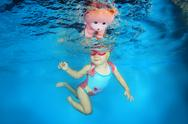 2 years girl with a toy learning to swim underwater in the pool, Stock Photos