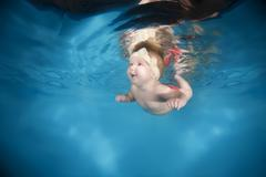7 months infant girl learning to swim underwater in waterbaby class in the pool Stock Photos