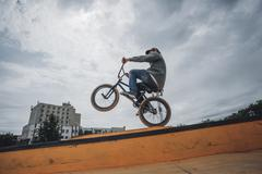 Low angle view of teenage boy performing stunt on ramp against cloudy sky Stock Photos