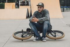 Teenage boy contemplating while sitting on bicycle at skateboard park Stock Photos