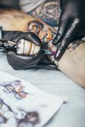 Artist tattooing multi colored design on human hand Stock Photos