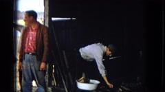 1967: several men are standing in the doorway of a barn talking and smiling Stock Footage