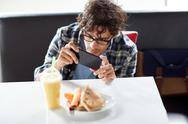 Man with smartphone photographing food at cafe Stock Photos