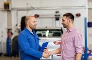 Auto mechanic and man shaking hands at car shop Stock Photos
