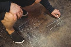 Glassblower drawing diagram on floor Stock Photos