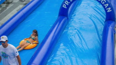 Two girls are going down a water slide on swim rings Stock Footage