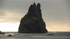 Reynisdrangar sea stack bird nest colony breaking waves Reynisfjara Vik Iceland Stock Footage