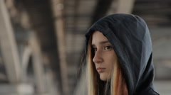 A close up of a teenage girl in a hoody with the hood on and loose multicolored Stock Footage