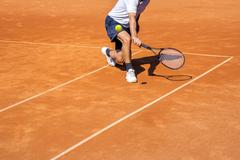Male tennis player in action on the clay court on a sunny day Stock Photos