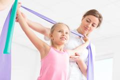Little girl doing exercises with her physiotherapist Stock Photos