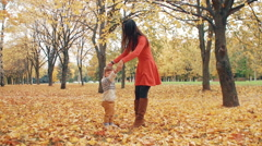 Young beautiful mother turns her cute little son around holding his hand in Stock Footage