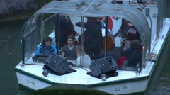 Tourists and a classical music band are sailing on a small boat together Stock Footage