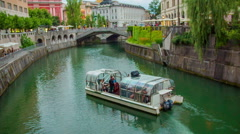 Small boat is sailing on the river Ljubljanica towards the three bridges Stock Footage