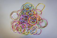 Directly above shot of multi colored rubber bands on gray background Stock Photos