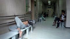 Boy fell asleep on bench on hospital corridor Stock Footage