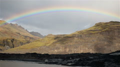 Brilliant bright rainbow over Solheimar glacier fast moving clouds Iceland Stock Footage
