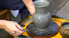 Man makes patterns on the clay pot Stock Footage