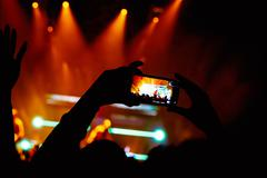 Hand with a smartphone records live music festival, Taking photo of concert Stock Photos