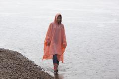 Woman wearing raincoat walking at lakeshore in rainy season Stock Photos