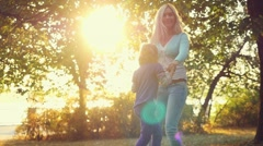 Happy mother and daughter spinning in summer park on sunshine background in Stock Footage