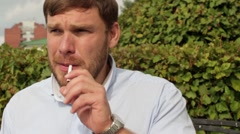 Man smokes on the bench in the park Stock Footage