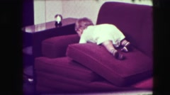 1942: cute baby is trying to catch an object over the couch NEW YORK Stock Footage
