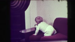 1942: baby reaches for snow globe adeo man catches baby from falling off couch Stock Footage