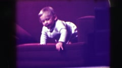 1942: blonde haired toddler climbs down from a couch and bumps his head.  Stock Footage