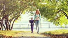 Happy family mother and child little daughter walking on autumn park in Stock Footage