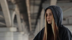 Hipster girl in a hoody with the hood on and loose multicolored hair against the Stock Footage