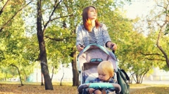 Mother carries her son in a pram in autumn park in slowmotion. 1920x1080 Stock Footage
