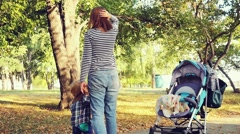 Yong mother with child son in autumn park walking next to pram in slowmotion Stock Footage