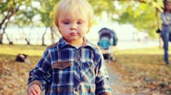 Cute baby boy walks in the park in slowmotion on suny autumn day. 1920x1080 Stock Footage
