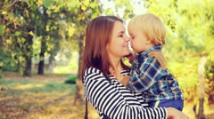 Mother and her child enjoy the early autumn in slowmotion. Mom kisses her son Stock Footage