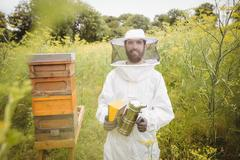 Portrait of beekeeper holding bee smoker Stock Photos