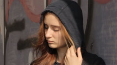 A teenager girl in a hoody with the hood on and multicolored hair against the Stock Footage