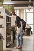 Side view of woman searching for book at library Stock Photos