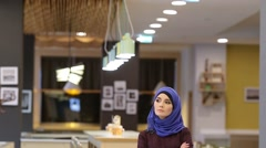 Muslim woman in a modern oriental dress standing in the foyer of the restaurant Stock Footage