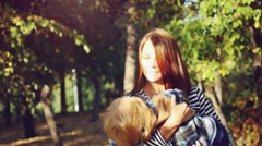 Young mother and her baby fall fun holds in hands in autumn park in slowmotion Stock Footage